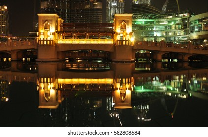 Dubai night view. bridge over artificial pond in city center.