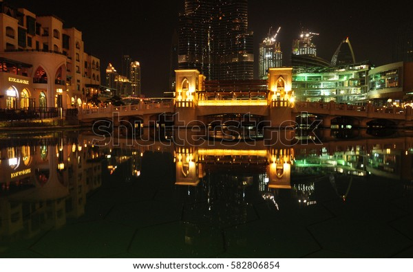 Dubai night view. bridge over artificial pond in city center.