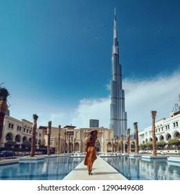 DUBAI - OCTOBER, 2018: Portrait of beautiful woman wearing long dress walking in Dubai. View from behind.
