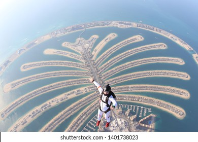 Dubai. Skydiving men stand on Dubai palm in free fall. Skydive Dubai. Skydiving and free fall in summer
