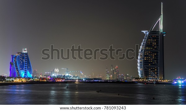 Dubai skyline with Burj Al Arab hotel at night timelapse. View from jumeirah beach. Dubai marina towers on background. Burj Al Arab is a luxury 5 stars hotel built on an artificial island in front of