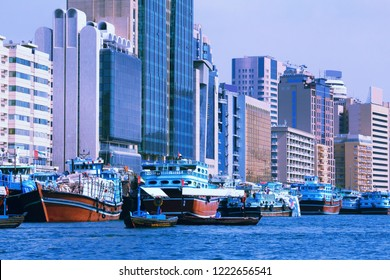 Dubai skyline in Deira district. Dhow ships in harbor. Retro filtered style.