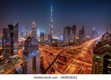 Dubai skyline during sunrise with shining traffic road, United Arab Emirates.