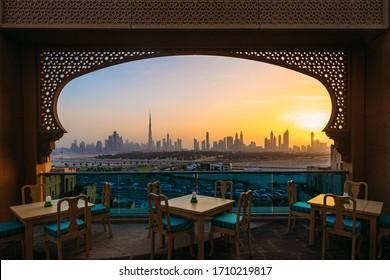 Dubai skyline view through oriental balcony and table setup ; Ramadan themed windows