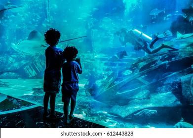 Dubai. Summer 2016. Two boys looking at a large aquarium in hotel Atlantis The Palm. Children watchig fishes at a big aquarium.