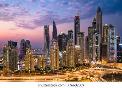 Dubai sunset skyline. Dubai Marina skyscrapers. Cayan tower, Princess tower, Marina 101, The Torch tower. Sheikh Zayed road. Tallest Dubai buildings. Beautiful sunset sky. Dubai luxury property.