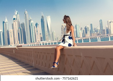 Dubai travel tourist woman on vacation in the Palm Jumeirah, looking at panoramic view of skyscrapers. UAE summer destination.