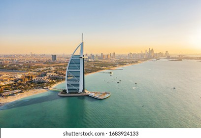 Dubai, UAE - 03/25/2020 : Aerial view of Burj Al Arab Jumeirah Island or boat building with downtown skyline. Financial district in urban city. Skyscrapers at sunset.