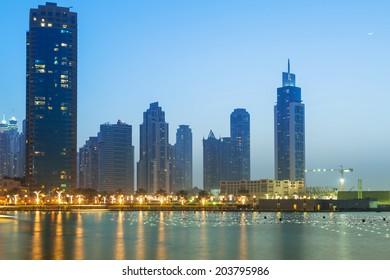 DUBAI, UAE - 1 APRIL 2014: Downtown of Dubai at dusk, UAE. Dubai is the most populous city in the United Arab Emirates with 2,1 million people.
