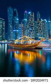 Dubai, UAE – 10 14 2020: Night view to Dubai Marina panorama, and traditional wooden UAE boat. Luxury skyscrapers represent modern Dubai. Amazing colors reflect on the water. Shot at blue hour.