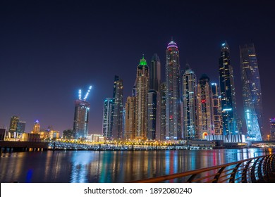 Dubai, UAE – 12 15 2020: Night view to Dubai iconic skyscrapers panorama. Amazing illumination of the buildings reflected in the Persian Gulf sea. Shot at blue hour.