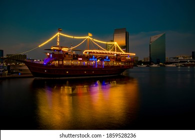 Dubai, UAE, 13 November 2020: View of Dubai Creek in Old Dubai in Al Seef Area. Beautifully lit dhow cruise docked with a stunning reflection on the water.
