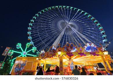DUBAI, UAE - 16 DECEMBER 2016: Tourists enjoy the funfair at Global Village (Dubailand), a 1,6 million m2 park that is the world's biggest theme park & attracts 5 million visitors a year. Editorial