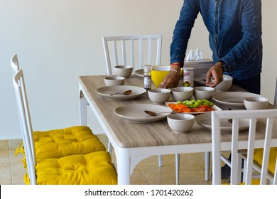 Dubai, UAE 2020: Man arranging dinning table with food and crockery items. he Scandinavian styled furniture with yellow chair cushions and grey color crockery can be seen in the image