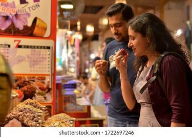 Dubai, UAE, 2020. Tourist doing walking tour & smelling aromatic spices & herbs on display at the famous Spice Souk market in Baniyas Street, in locality of Al Ras, Deira, Dubai. Shopping for Ramadan