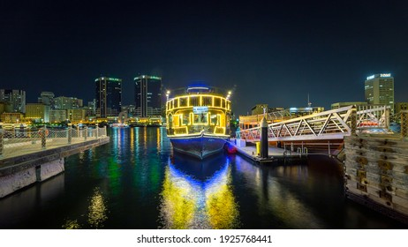 Dubai, UAE, 23 December 2020: View of Dubai Creek in Old Dubai in Al Seef Area. Beautifully lit dhow cruise docked with a stunning reflection on the water.