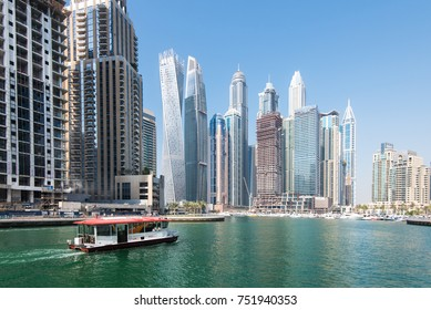 DUBAI, UAE - 31OCT2017: A Water Bus moving towards thetowers of Dubai Marina including (l-r) Cayan, Damac Heights, Marriott, Emirates Crown, Princess Tower, Torch, Elite Residences, Marina Heights