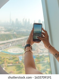 Dubai, UAE - 7 May, 2018: Girl taking photo of Dubai skyline from iPhone during the day