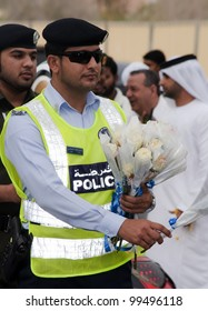 "DUBAI - UAE - APRIL 06 2012: Member of Dubai Police distributing roses during the ""March For Peace"" event organized by Dubai Islamic Department and Govt. of Dubai on April 06 2012 in Zabeel, Dubai."