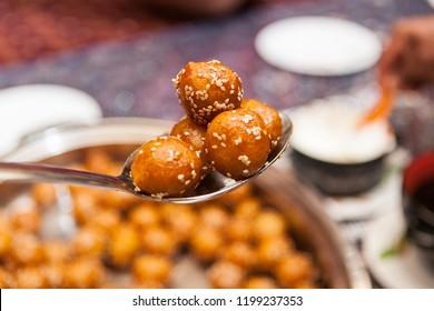 DUBAI, UAE - APRIL 5, 2014: Luqaimat doughnut balls on a spoon, with more luqaimat on a tray in the background.  Luqaimat is a popular Arabian dessert that is often eaten during Ramadan.