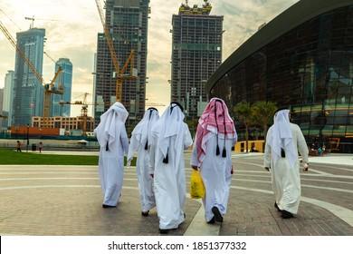 DUBAI, UAE - APRIL 5, 2020: Arabic men wearing traditional white clothes walking in Dubai downtown, United Arab Emirates