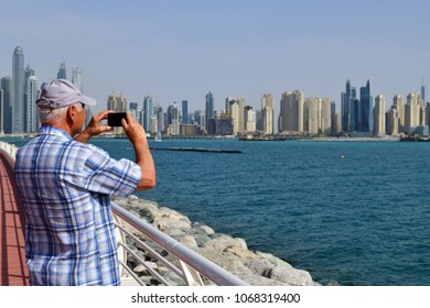Dubai, UAE - April 8. 2018. Tourists take pictures Dubai Marina attractions