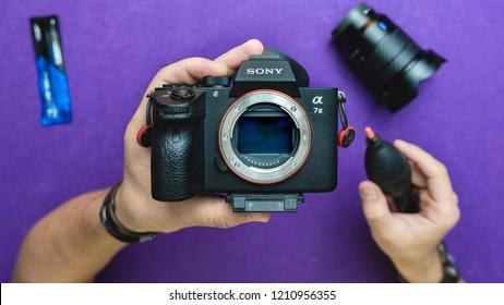 Dubai, UAE - August 2018 : Cleaning Sony A7 iii Mirrorless Camera Sensor using an air blower