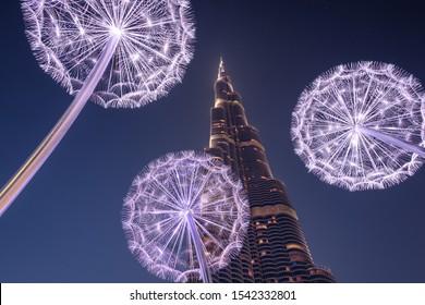 Dubai, UAE - August 28 2018: Burj Khalifa at blue hour with metal sculptures lit up surrounding the worlds tallest building