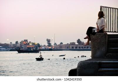 DUBAI, UAE - CIRCA 2014: a girl sits on the stair with view on Dubai Creek on a subset in Dubai, United Arab Emirates.
