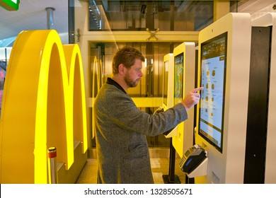 DUBAI, UAE - CIRCA JANUARY, 2019: man use self-ordering kiosks at McDonald's restaurant in Dubai International Airport.