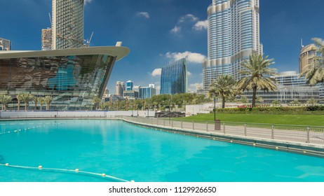 DUBAI, UAE - CIRCA MARCH 2018: Park with fountain pool timelapse hyperlapse. Dubai Opera and modern skyscrapers on background in Downtown, Dubai, United Arab Emirates