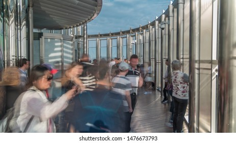 Dubai, UAE - CIRCA MARCH 2019: Tourists meet sunrise at the observation deck on the 125 floor of Burj Khalifa tower timelapse. Crowd making photos from the top