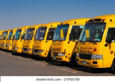 DUBAI, UAE - DEC 13: An oblique perspective of 8 yellow Arabic school busses on Dec 13, 2013 in Dubai, UAE.