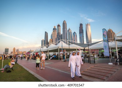 Dubai, UAE - December 15th 2015 - Local and tourists enjoying a later afternoon in Dubai, with Marina Dubai skyline in the background. United Arab Emirates