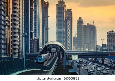 DUBAI, UAE - DECEMBER 16, 2015: Dubai's downtown architecture in the evening with metro monorail train arriving at the station.