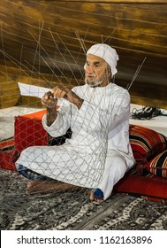 DUBAI, UAE - DECEMBER 4, 2017: The old man is weaving a fishing net to meet guests in the pavilion  of United Arab Emirates, Global Village
