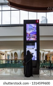 Dubai, UAE - Feb 16, 2019: Arabian woman in traditional clothes uses search electronic system by Dubai mall.