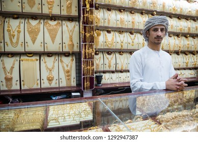 DUBAI, UAE - February 14, 2018: A jewelry reseller at work in a shop at the Dubai Gold Souk market, United Arab Emirates