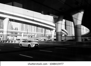 Dubai, UAE February 20, 2018: Lexus rides on the highway against the backdrop of road junctions and overpasses. black and white photo