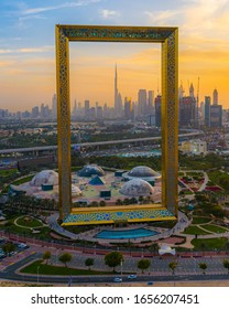 Dubai, UAE - February 2020: Amazing sunset view of the world's largest frame made from gold in Dubai, UAE; Dubai frame at sunset featuring Dubai skyline on a cloudy day