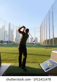 Dubai, UAE, February 2021-Man playing golf at Top Golf in Dubai