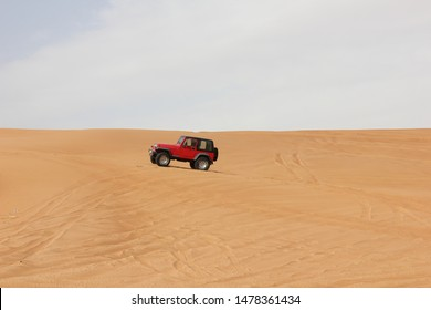 Dubai, UAE - February 24, 2019: A red 4x4 or 4WD vehicle with a short wheel base drives through desert sand dunes in an offroad or off road desert safari in Dubai, United Arab Emirates (UAE).