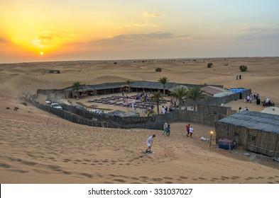 DUBAI, UAE - FEBRUARY 28 2014: Colorful sunset behind a bedouin camp after the traditional desert safari in Dubai UAE
