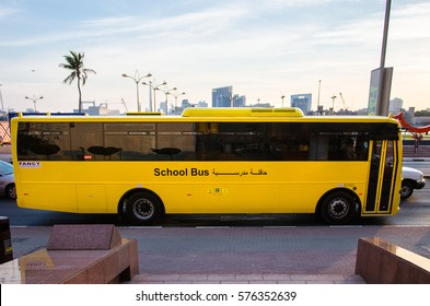 DUBAI, UAE - FEBRUARY 6, 2017: A yellow school bus is waiting for green light, side view.