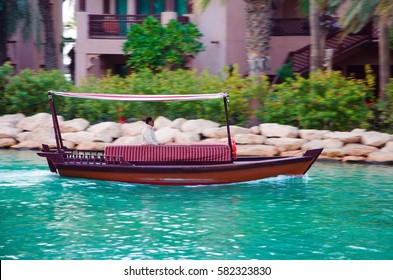 DUBAI, UAE - FEBRUARY 9, 2017: Middle eastern man is driving a traditional arabic wooden ship (Abra) used for movement of tourists in Madinat Jumeirah (Resort)
