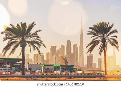 DUBAI, UAE - JAN 18, 2019: Palm trees at a parking lot with Burj Khalifa and the city center in background.