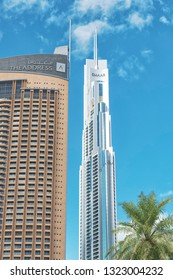 DUBAI, UAE - JAN 20, 2019: The Address hotel in the Dubai mall district with clear sky and a green palmtree. Window cleaners at Emaar building