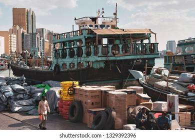 DUBAI, UAE - JAN 20, 2019: Busy harbor in Deira district in Dubai with a traditional freight ship meeting modern buildings. Dubai canal, Deira