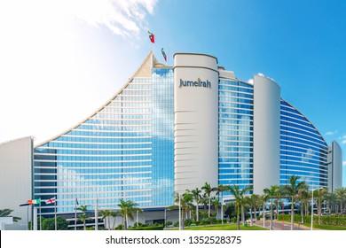 DUBAI, UAE - JAN 20, 2019:  Jumeirah beach hotel during a warm sunny day. Green palms and blue sky.