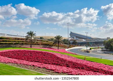 DUBAI, UAE - JAN 20, 2019:  Mall of Emirates with the ski slope structure also visible the roof of the station Emirates. In the foreground pink flowers and green lawn betwwen the roads.